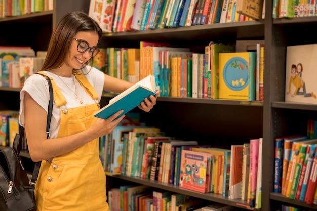 Adolescente estudante lendo livro encostado na prateleira Foto gratuita