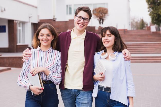 Adolescente, estudante, menino, abraçar, menina, colegas, e, olhando câmera Foto gratuita