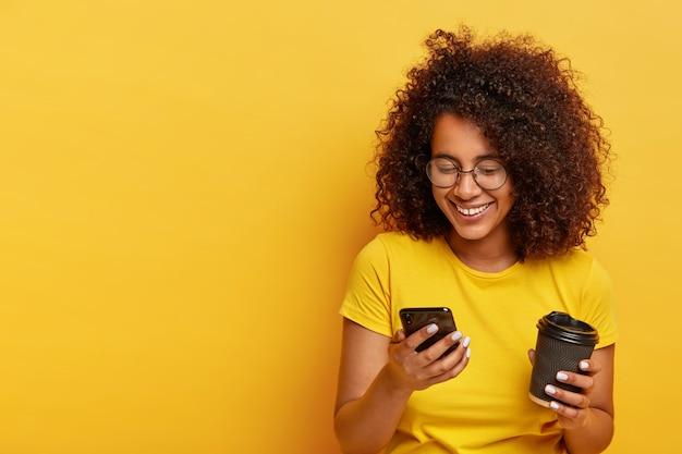 Adolescente feliz com cabelo encaracolado, segura um telefone celular moderno, café para viagem, pede um táxi via aplicativo online, digita mensagem de texto, usa roupas amarelas. pessoas, estilo de vida moderno e tecnologia Foto gratuita
