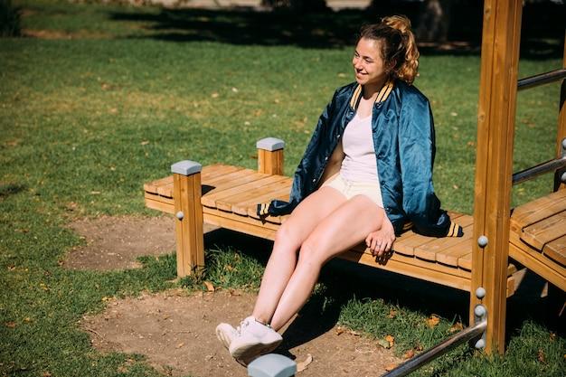 Adolescente feliz sentado no banco no parque Foto gratuita