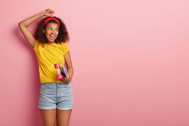Adolescente hippie com cabelo encaracolado posando em uma camiseta amarela Foto gratuita