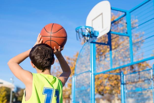 Adolescente jogando uma bola de basquete no aro por trás Foto Premium