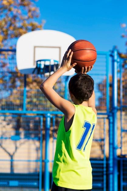Adolescente jogando uma bola de basquete no aro Foto Premium