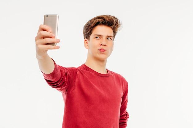 Adolescente jovem atraente faz uma selfie com smartphone na Foto Premium