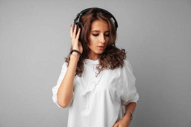 Adolescente jovem ouvindo música com seus fones de ouvido Foto Premium