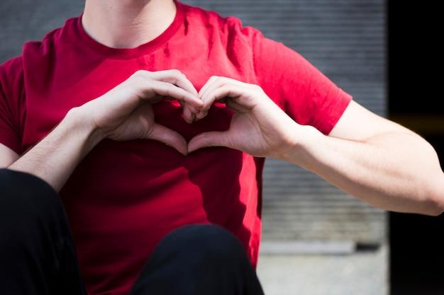 Adolescente masculino, mostrando, forma coração, com, mãos Foto gratuita