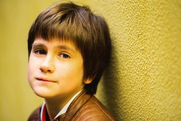 Adolescente menino posando contra um fundo de parede amarelo Foto Premium