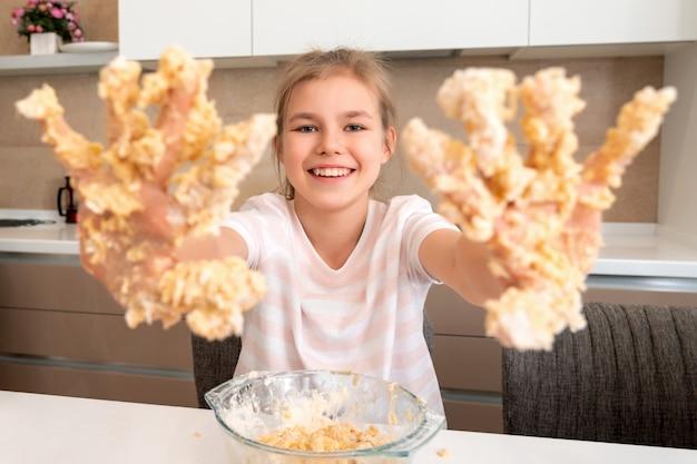 Adolescente mostra as mãos sujas na massa se divertindo na cozinha Foto Premium
