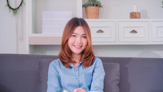 Adolescente, mulher asian, sentimento, feliz, sorrindo, e, olhando câmera, enquanto, relaxe, em, dela, sala de estar Foto gratuita