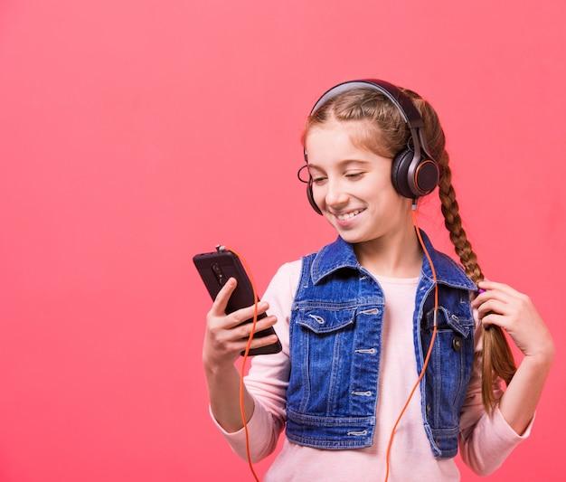 Adolescente, ouvindo música em fones de ouvido grandes Foto Premium
