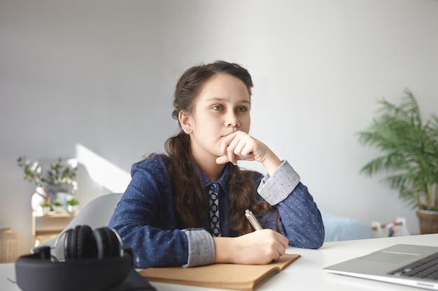 Adolescente pensativa em uma camisa casual sentada na mesa em casa com um laptop e fones de ouvido, fazendo a lição de casa, escrevendo uma redação no caderno Foto gratuita