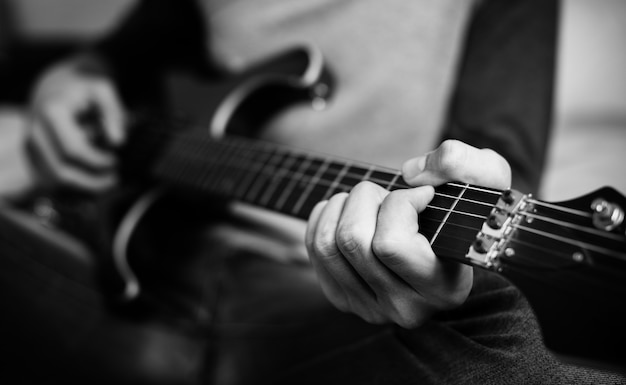 Adolescente que joga uma guitarra elétrica em um passatempo do quarto e no conceito da música Foto gratuita