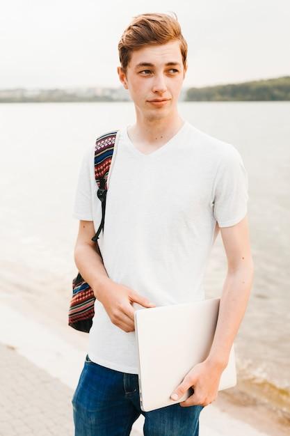 Adolescente segurando laptop à beira do lago Foto gratuita