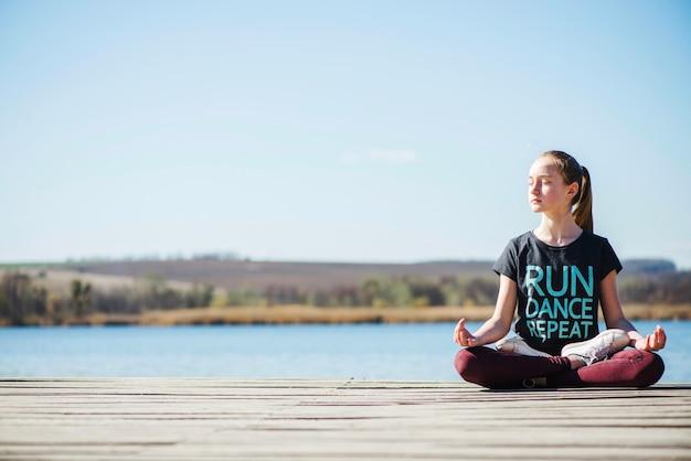 Adolescente sentado no pier na posição de lótus Foto gratuita
