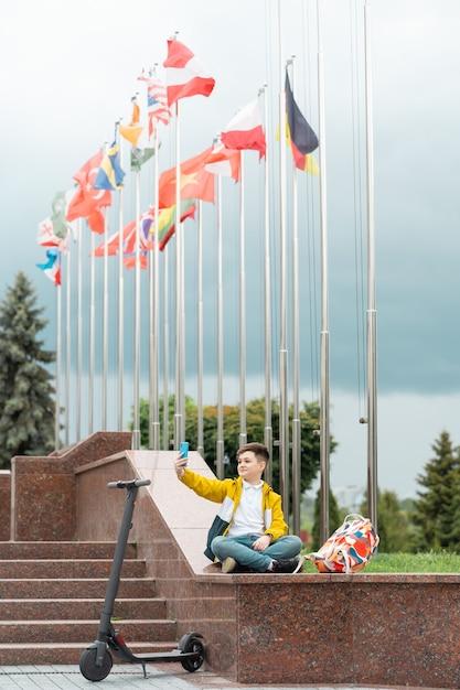 Adolescente sentado perto do prédio da administração Foto Premium