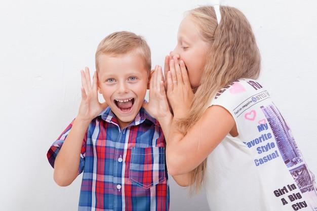 Adolescente sussurrando no ouvido de um adolescente secreto em fundo branco Foto gratuita