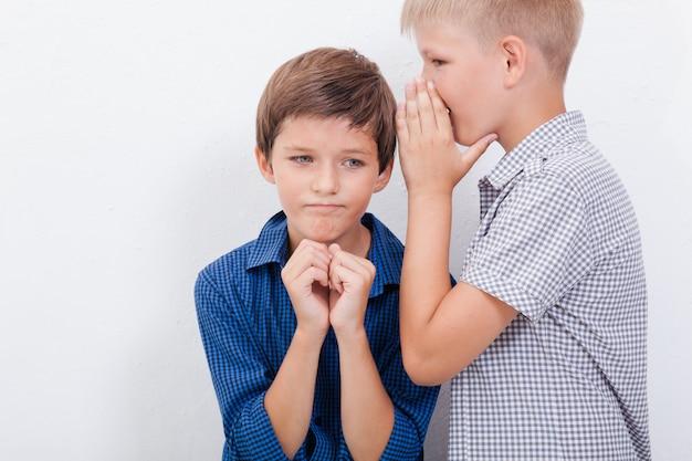 Adolescente, sussurrando no ouvido, um segredo para um amigo na parede branca Foto gratuita