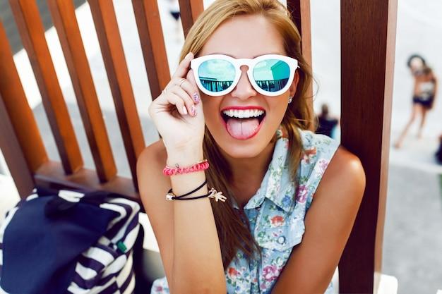 Adolescente usando óculos escuros e fazendo cara engraçada Foto gratuita