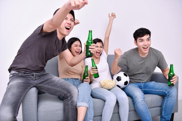 Adolescentes asiáticos assistindo futebol na televisão Foto Premium