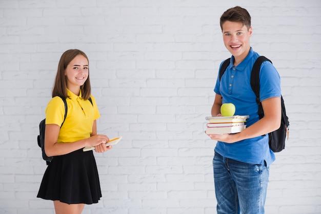 Adolescentes com mochilas e cadernos Foto gratuita