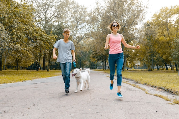 Adolescentes correndo com cachorro branco husky na estrada no parque Foto Premium