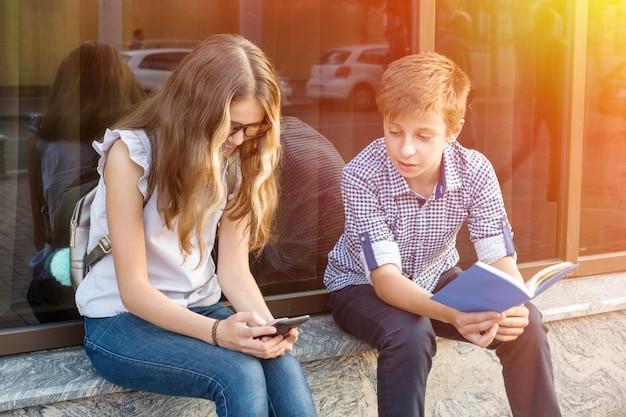 Adolescentes de crianças, lendo o livro e usando o smartphone. Foto Premium