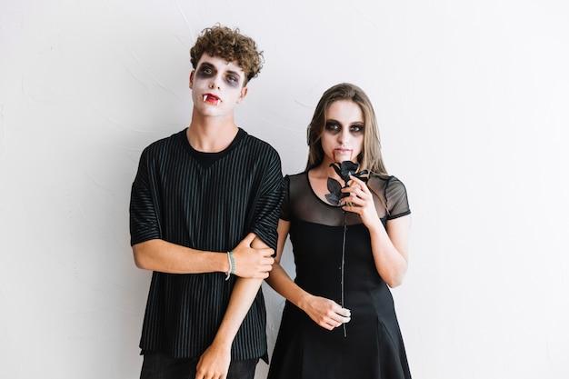 Adolescentes, em, roupas pretas, e, assustador, vampiro, severo, ficar, com, rosa preta Foto gratuita
