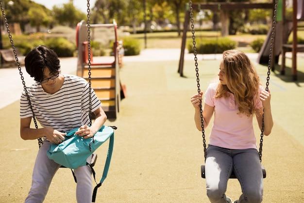 Adolescentes multiétnicas sentado em balanços Foto gratuita