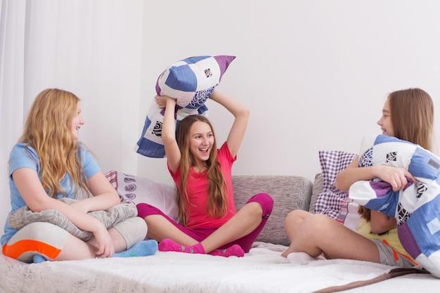 Adolescentes se divertindo e lutando com almofadas Foto Premium