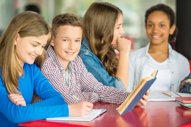 Adolescentes sentado à mesa no café e fazendo lição de casa. Foto Premium