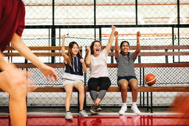 Adolescentes torcendo os meninos jogando basquete Foto Premium