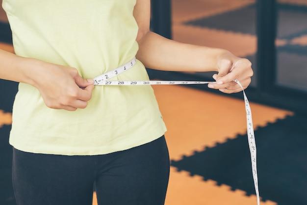 Adolescentes usam suas próprias cintas de medição de cintura. forma de controle de si mesmo após exerc Foto Premium