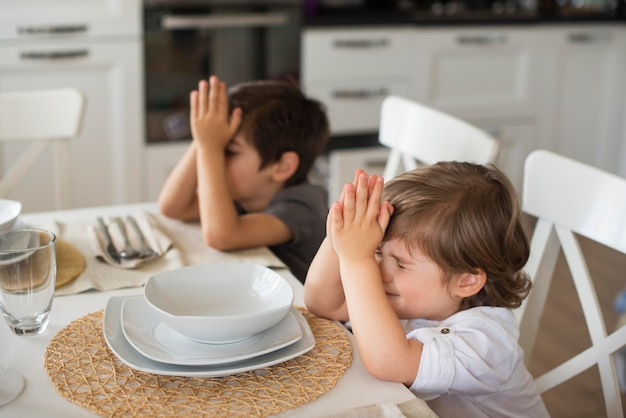 Adoráveis crianças rezando em casa Foto gratuita