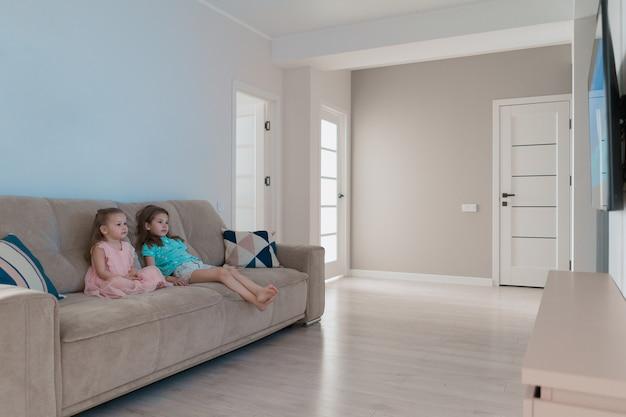 Adoráveis irmãs assistindo tv em casa Foto gratuita