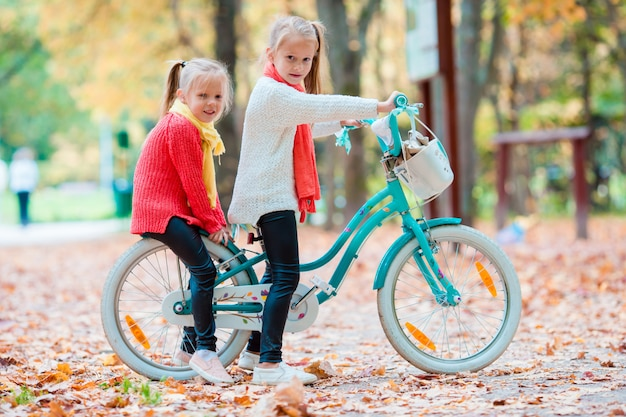 Adoráveis meninas andando de bicicleta no lindo dia de outono ao ar livre Foto Premium
