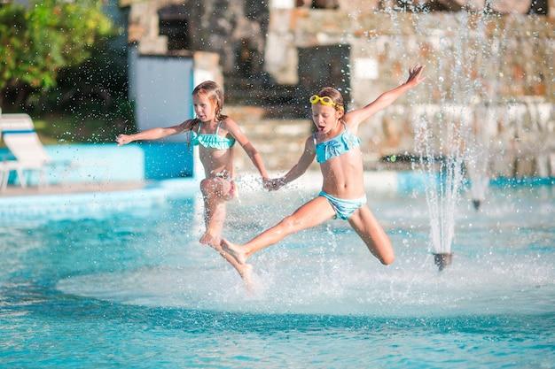 Adoráveis meninas brincando na piscina ao ar livre Foto Premium