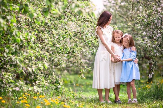 Adoráveis meninas com jovem mãe no jardim desabrocham cereja em lindo dia de primavera Foto Premium