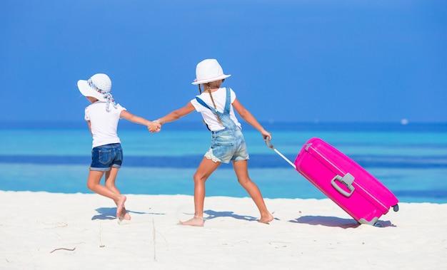 Adoráveis meninas com mala grande na praia tropical branca durante as férias de verão Foto Premium