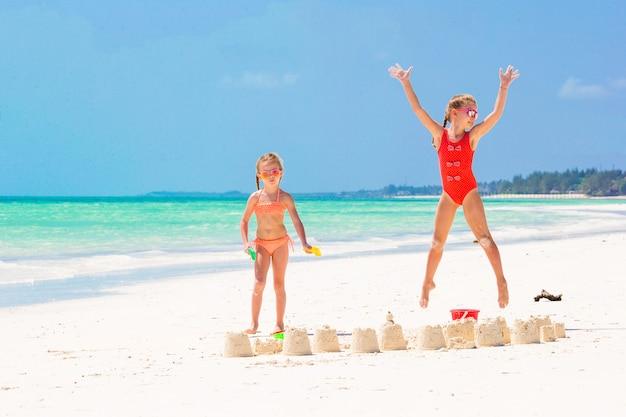 Adoráveis meninas durante as férias de verão. crianças brincando com brinquedos de praia na praia branca Foto Premium