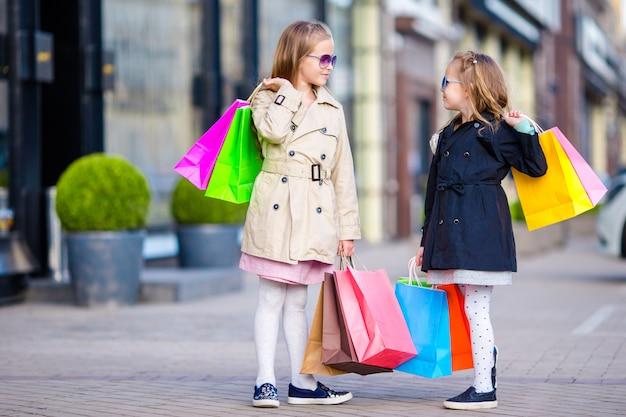 Adoráveis meninas em compras. retrato de crianças com sacolas de compras. Foto Premium