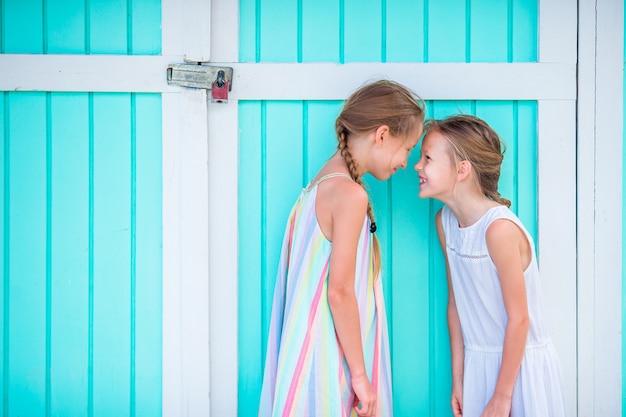 Adoráveis meninas nas férias de verão, tradicional casa do caribe colorida Foto Premium