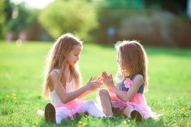 Adoráveis meninas no dia de primavera ao ar livre, sentado na grama Foto Premium