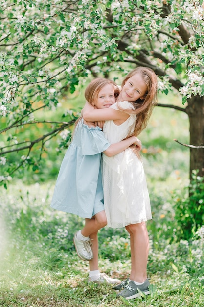 Adoráveis meninas no jardim de macieira florescendo na primavera Foto Premium