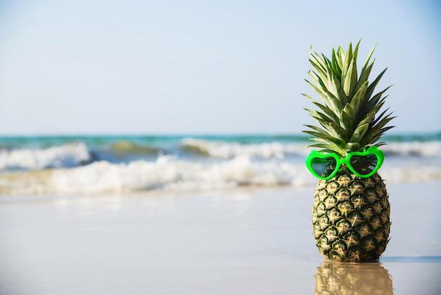 Adorável abacaxi fresco colocar óculos de sol de forma de coração na praia de areia limpa com a onda do mar - fruta fresca com conceito de férias de sol de areia do mar Foto gratuita
