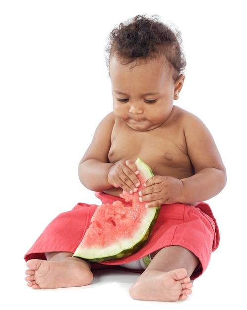 Adorável bebê comendo melancia sobre fundo branco Foto Premium