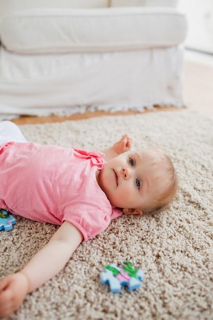 Adorável bebê loiro brincando com peças de quebra-cabeça enquanto deita em um tapete Foto Premium