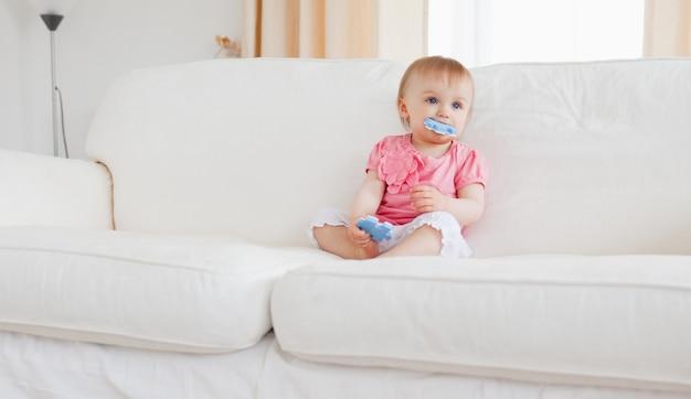 Adorável bebê loiro brincando com peças de quebra-cabeça enquanto está sentado em um sofá Foto Premium