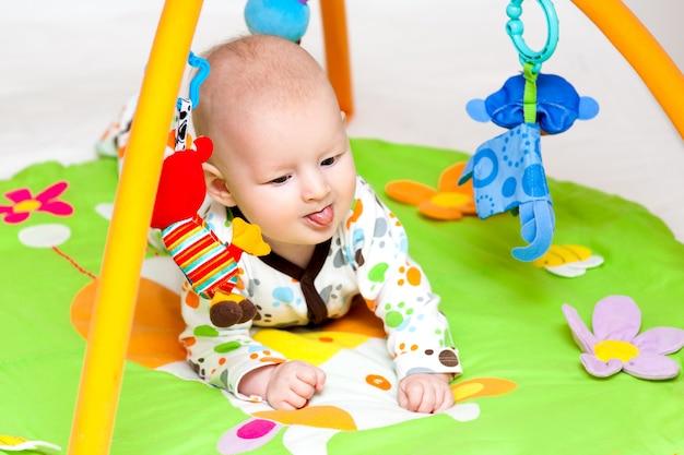 Adorável bebê se divertindo com brinquedos no tapete colorido. Foto Premium