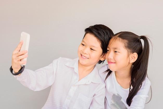 Adorável casal asiático escola crianças estão tomando selfie Foto gratuita