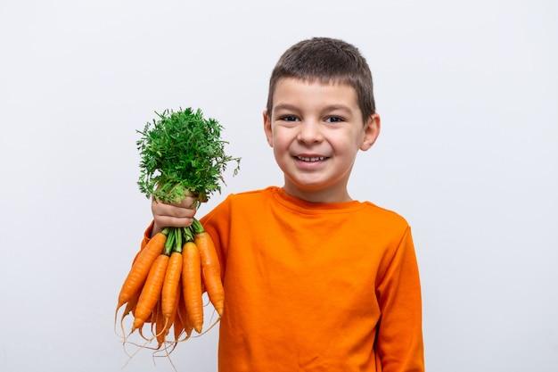 Adorável criança com cenoura. vegetais orgânicos saudáveis para crianças. menino garoto segurando uma cenoura nas mãos. Foto Premium